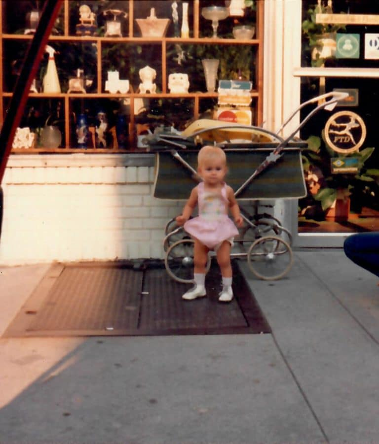 baby standing in front of flower shop